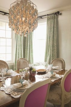 Golden chandelier, green drapery and hot pink chairs. Very glamourous.