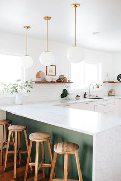 loving the green beneath the countertops, contrasting with the wooden stools, and the gorgeous white marble