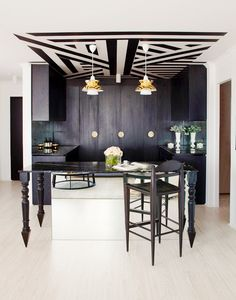 Black and white kitchen with industrial lighting and patterned ceiling