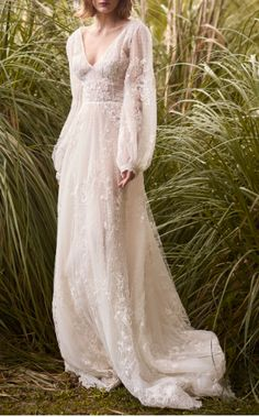 This Costarellos Bridal Embroidered Lace Ethereal Gown features a v-neckline and long bishop sleeves.