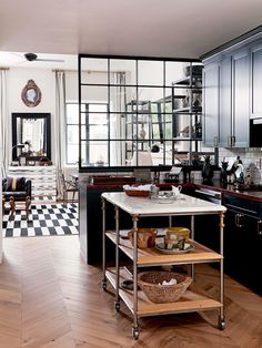 Retro inspired kitchen with black cabinents, herringbone floors, and a wood island cutting station