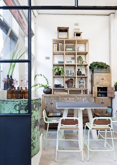 Rustic industrial dining area. Love the distressed drum come side table, old bottles, repurposed timber and cube shelving.