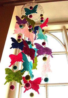 Felt butterflies sewn through a woollen thread with woollen balls