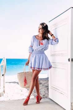 Casual beach outfit: blue & red embroidered tunic & a mini skirt + red pom pom sandals + oversized straw beach tote