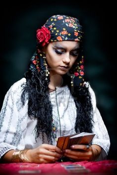 a portrait of a gypsy fortune teller, sitting at a table and looking at the tarot cards that she holds in her hands.
