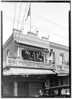 Two-story building in Ferguson Alley, part of Chinatown, Los Angeles, November 1933 | Photograph of a two-story building in Ferguson Alley, part of Chinatown, Los Angeles, November 1933. The two-story brick building can be seen at center. Flowers can be seen on a second-story balcony, where a Chinese man can be seen sitting in a chair. A metal gate covers a shop window on the first floor. Two automobiles can be seen in the foreground at right, and a man is visible ...