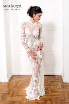 Anna Romysh skyler, collectie 2016 nb, De transparante kant van deze trouwjurk is van een ongekende schoonheid. Juist door de transparantie komt dit extra tot uitdrukking. Let ook op de rijke versierde voorzijde met luxe stenen. Het hoog gesloten lijfje met lange mouwen en soepel vallende rok geven de jurk een luxe uitstraling. #couture #exclusief #extravagant #glamour #koonings
