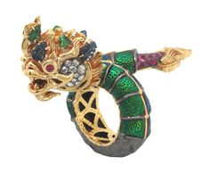 Adorning the beauty of nature, Lotus Arts de Vivre turns nature into this unique Naga design by covering the body with the thorax of scarab beetles. This Naga ring is made of 9K gold & black rhodium sterling silver set with white rose-cut diamonds, carved emeralds, carved sapphires, and facetted rubies.  Size #55 Dimension: 2.9x4.8x5.5 cm.