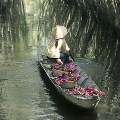 Vietnamese woman rowing boat loaded with waterlily flowers