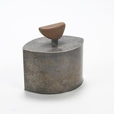 Lot 426: Harry Bertoia. lidded vessel. c. 1942, silver, cherry. 4 w x 3 d x 3¾ h in. result: $9,600. estimate: $7,000–9,000. Harry Bertoia became the director of the metal studio at Cranbrook in 1937. Bertoia's work can be classified in two ways, ranging from fully realized and refined silverwork to irregular biomorphic forms. This lidded vessel and creamer are two pieces of a three-piece service illustrating Bertoia's biomorphic style. Provenance: Acquired directly from the artist | ...