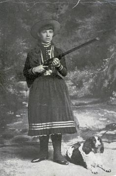 A portrait of young Annie Oakley (1860-1926) with medal pinned to chest & dog at her side.