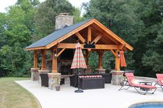 Garden Idea: Covered Pavillion w/ cool front beam detail, stone fireplace + hearth, posts have stone bases. Probably ceiling fans, lights, could install foggers for heat & heat lamp for cold & add heavy drapes on sides as well. Back should be solid so no peeking through to alley. via www.CharlotteRemodelingCompany.com