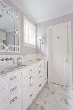 White and Lavender bathroom boasts a white trellis mirror, lining a lavender painted wall, placed over an extra-wide single washstand fitted with stacked drawers adorned with rectangular drop pulls topped with gray and white marble. Lavender Paint, Lavender Walls, Lavender Bathroom, Purple Bathrooms, Light Purple Walls, White Walls, Purple Ceiling, Gray Walls, Diy Bathroom
