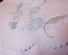 Detalle de un juego de cama bordado en hilo de varios colores sobre fondo rosa