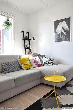 värikäs,olohuone,sohva,dlm,sohvatyynyt,matto,hylly,taulu,julisteet