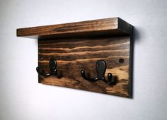 This small wall mount key hook rack has a shelf and 2 double hooks. It's perfect for that small space in your entryway or kitchen for hanging your purse and keys. This rustic wood rack is stained and fully sealed to protect the wood. This piece has 2 predrilled holes and comes with screws and anchors for easy hanging. This will be handmade to order so there may be slight variations in color/finish as well as grain pattern. Every piece of wood is unique. Back is unfinished.