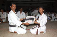 karate sankar is  giving the black belt and certificate his student Rashmikaa.