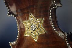 In a Monday, April 9, 2012 photo, the back of a violin showing a Star of David is shown on display at the Violins of Hope exhibit at UNC Charlotte in Charlotte, N.C. Eighteen violins recovered from the Holocaust and restored by  Israeli violin maker Amnon Weinsten make their U.S. debut on Sunday, April 15. Some were played by Jewish prisoners in Nazi concentration camps, while others belonged to the Jewish Klezmer musical culture. Photo: Chuck Burton, Associated Press