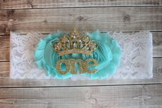 Two 2.5 inch shabby flowers in mint, gold tiara with pink rhinestones, the word one in gold glitter letters on 2 inch white stretch lace. Felt backed for comfort.  All items in our shop are handmade and custom fit for each order. Sized 16 to fit average one year old.   Please send a message with any custom design/color requests.   Please read shop policies before placing orders. All orders ship 3-5 business days.  ATTENTION/WARNING: This item contains small parts that pose a choking hazard…