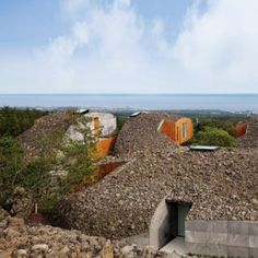 Volcanic rubble is scattered across the curved rooftops of these villas by Japanese architect Kengo Kuma on Jeju Island, South Korea