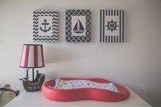 Trocador emborrachado na cor vermelha com abajur em forma de barquinho e quadrinhos na parede tema nautico