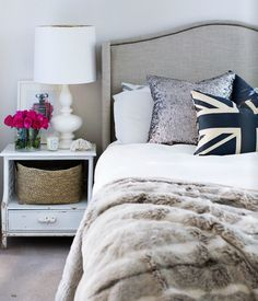 Plain and simple bedroom with a pop of fun in the navy British flag pillow and arrangement of pink roses on the nightstand