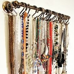 I love this idea. Use a towel bar and shower curtain hooks to hang necklaces from.