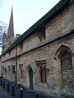 """Great Almshouses, Church Lane, Burford, Oxfordshire; built for Richard Neville, 16th Earl of Warwick (""""The Kingmaker"""") in 1457. In the background is the spire of St John the Baptist parish church."""