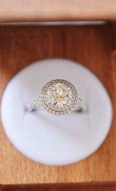 This stunning engagement ring features a mesmerizing double halo of pavé-set diamonds and elegant double claw prongs.