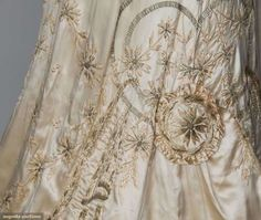 """2-piece, white satin, bodice of Point de Gaz lace, silk floss & silver metallic thread embroidery, long train basted onto trained skirt, B 34"""", W 22"""", Skirt L 40""""-68"""","""
