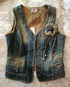 Denim gilet hand embroidered with micro bronze sequins and studs. Frayed armholes. Flowers denim applicate. Vintage print on the back. 3 hooks closure on the front. Only pieces. Chest: 92cm. H: 54cm