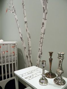 Nursery design with gray walls paint color, white modern crib, birch tree wall mural and mercury glass candle holders.