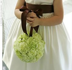 The bride's niece wore an ivory sleeveless dress with a chocolate satin sash. She carried a green pomander, which matched those hanging from the chairs along the aisles.