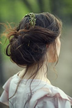 Messily rolled and pinned hair with a decoration made from braided rosemary. Love it.