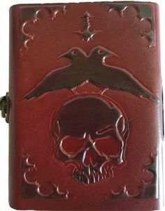 Handmade paper and embossed leather journal feature two ravens over a skull, done in two tones to highlight the image. The back cover is a grand flying raven over a great tree. Binding edge has real l