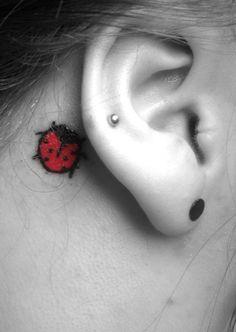 lady bug bird ear tattoo