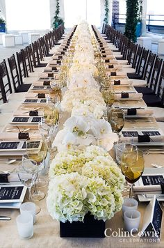White hydrangeas and orchids come together to create a statement-making centerpiece. Low Centerpieces, Wedding tabletop, Flowers || Colin Cowie Weddings