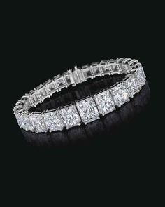 AN IMPRESSIVE DIAMOND BRACELET, BY CARTIER Designed as a graduated line of twenty-seven rectangular brilliant-cut diamonds, weighing from approximately 4.87 to 0.95 carats, 6 7/8 ins., mounted in platinum, in a Cartier red case and outer box
