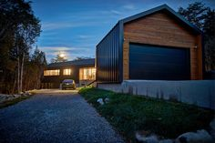 Black Garage Door With Cedar Siding And Metal Exterior Design Along With Mounting Lamps Decoration And Pebbles Sidewalk A Mixture of Cedar Siding and a Metal Exterior L-Shaped House Home design