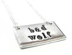 "Hand Stamped Aluminum Necklace - Bad Wolf - Doctor Who Inspired. ""Bad Wolf"" hand stamped on a tiny aluminum tag. The tag is approximately 3/8"" x 3/4"" and it comes on a 18"" silver plated dainty chain. Hypo-Allergenic Aluminum won't tarnish or turn your skin funny colors!. Great gift for any Doctor Who fan!. Quick shipping from California, US seller, ships in a gift box or bag."