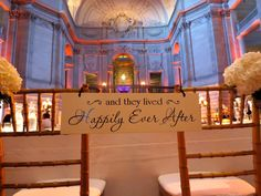 """""""and they lived happily ever after"""" sign strung on the bride and groom's reception chairs"""