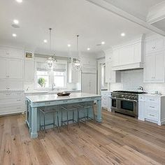 White Cabinets with Powder Blue Kitchen Island and Sawn Oak Wood Floors