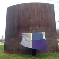 "Heidi Parkes with her art quilt, ""Night and Day,"" in front of Richard Serra's sculpture ""Reading Cones"" in Chicago's Grant Park. #quilt"