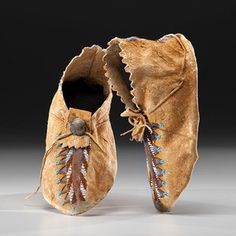 Apache Beaded Hide Moccasins From the US Children's Museum on the 19th Century sinew-sewn and beaded in color of amber, white, and light blue; hide coated with orange and blue pigment; angled cuff with pinked edges, length 10 in. ca 1900 Provenance: All proceeds of sale will benefit an endowed Faculty Chair in Child Rights at the University of San Diego School of Law; From the US Children's Museum on the 19th Century Price Realized Including Buyer's Premium $523 04/10/2015