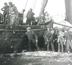 Fishermen on Worthing Beach. Group of men with their fishing boat. Boys on the boat are helpers. Pile of fish in a net in foreground. c1890
