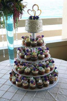 A wedding cupcake tower with a cutting cake on top by Freedom Bakery and Confections.
