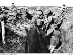 Foot inspection!   An officer of the 30th Battalion in the trenches near Zonnebeke, in the Ypres Sector, making the daily inspection of his mens' feet during the Third Battle of Ypres - September, 1917.   Left to right: unidentified (background); unidentified (partially obscured); Lieutenant (Lt) W Williams; unidentified; 3875 Private J P Ryan; Lt W C Abbott.