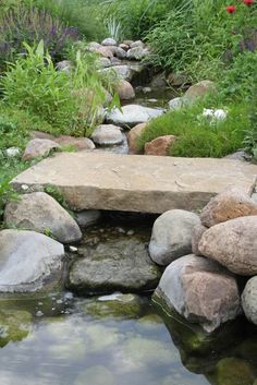 A close-up of the smaller foot bridge displays the intricate rock work that creates a babbling brook.