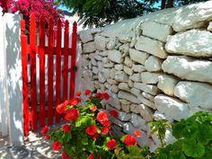 Red geraniums, red garden gate...