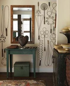A collection of vintage wire rug beaters adds visual drama to the walls of this rustic room. From Atticmag.com
